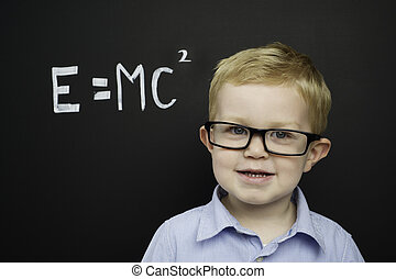 Smart young boy stood infront of a blackboard - Smart young...