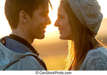 Close up of in love couple at sunset - Close up portrait of...
