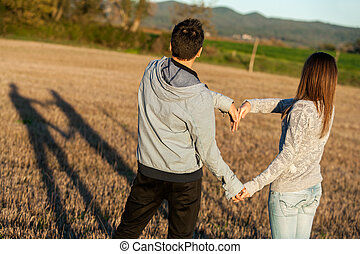 Couple making love sign with arms outdoors. - Young couple...