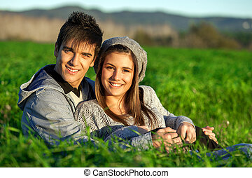 Portrait of teen couple sitting in grass field - Close up...