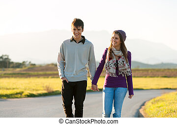Young couple wandering in sunny countryside. - Young couple...