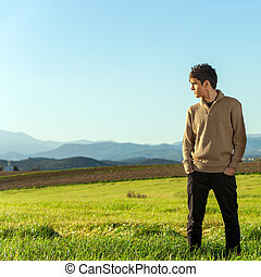 Young man standing in green field.