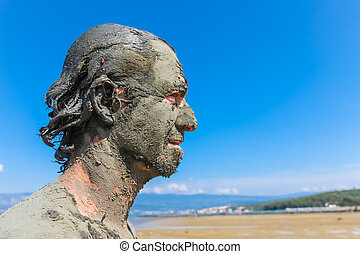Man smeared with healing mud on beach