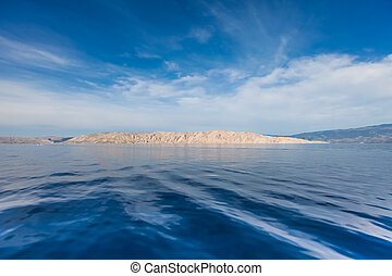 Views of Croatian island on blue sky and wavy sea