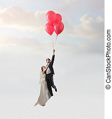 Married couple flying with balloons