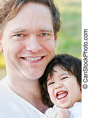 Handsome father smiling with his infant son, outdoors