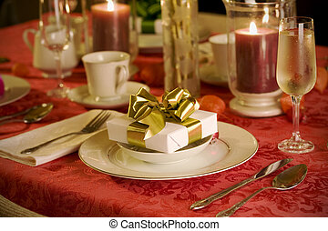 elegant Christmas table setting in red with gold gift as...