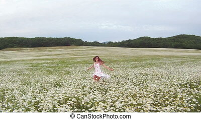 Blossoming daisies - Woman dancing and picking flowers in a...