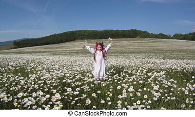 Dancing among daisies - Girl dressed in traditional...