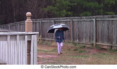 Keeping Dry - Teen girl in back yard on rainy day