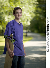 Young teenager holding his longboard during the summer
