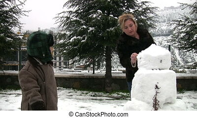 Mother and son with snowman
