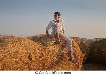 Man on haystack - Man sitting on haystack