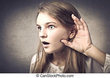 surprised girl listening with her hand near ear