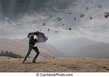 businessman in the storm with his umbrella