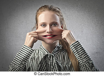 face elastic - blonde girl pulls cheeks on a gray background