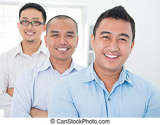 Southeast Asian business group standing in office