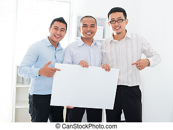 Asian business team holding a blank banner - Southeast Asian...