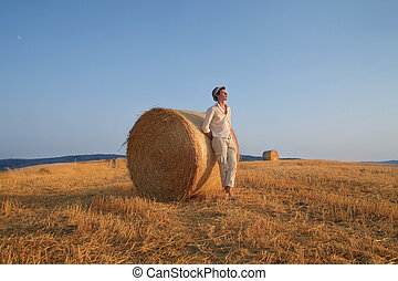 man hayfield - young man leaning on a bale of hay in tuscany