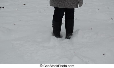 woman leg dig snow - woman legs stand in winter snowdrift...