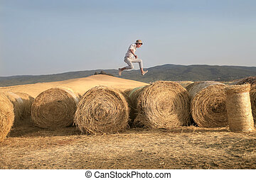 boy jumps in Tuscany - man jumping on hay bales in the...