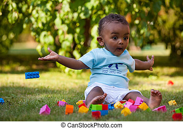 Little african american baby boy playing in the grass -...