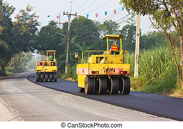Steamroller are crushed the asphalt road.