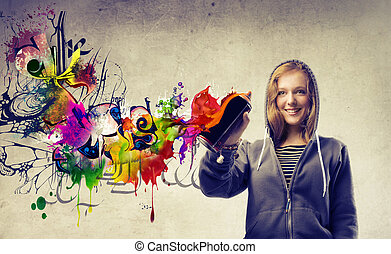 girl painting the walls with spray color