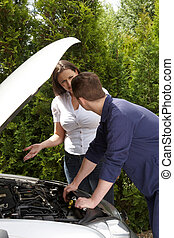 Mechanic repairing a car while talking to female customer