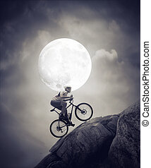 cycling in the moonlight - man with a bike ride in the...