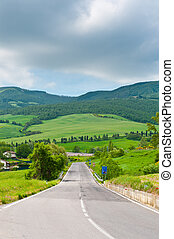 Green Meadows - Asphalt Road in Green Sloping Meadows of...