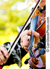 Woman Playing Violin - A close-up detail of a woman playing...