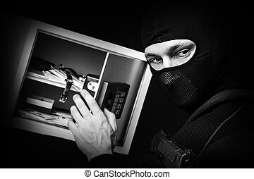 Professional burglar in black ski mask opened a small safe,...