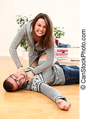 Angry woman choking a man lying on a floor