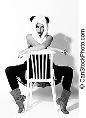 Young woman in panda suit smoking on a chair over a white...