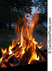 Raging inferno - Flames shoot from a pile of wood layered on...
