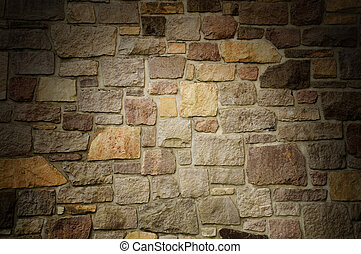 Masonry Wall of Multicolored Stone Lit Dramatically