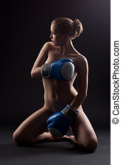 Naked woman sit in dark with boxing gloves