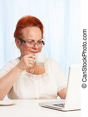 Internet browsing during breakfast - Senior woman reading...
