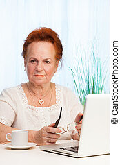 old woman sitting with laptop with puzzled expression on her...