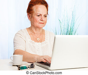 old woman using internet - nice old lady with white laptop