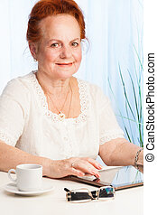 Smiling old woman with tablet pc - Smiling old woman sitting...