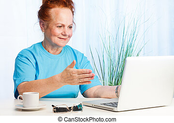 Senior lady pointing to the screen - Senior lady sitting...