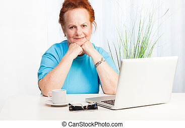 Confident senior woman with laptop smiling at camera