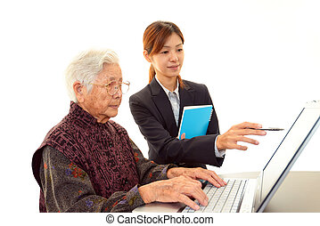Old woman enjoys computer - Teacher helping student on the...