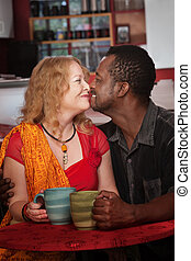 Mixed Eskimo Kiss in Cafe - Mixed middle aged couple do an...