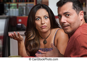 Annoyed Couple in Cafe - Annoyed Latino male and female...