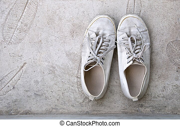 old dusty white sneaker on rough cement background