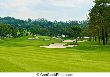 fairway in golf course with sand bunker tree and mountain in...