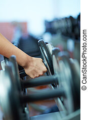 Taking barbell - Image of female hand taking barbell from...